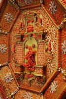 """Grande placca con l'Immacolata ( particolare), decorata con la tecnica del """"retroincastro"""", con elementi in corallo levigato fissati dal retro della struttura in metallo dorato, figure scolpite a tutto tondo nel corallo, smalto bianco ad alveolo, manifattura trapanese, inizio XVII secolo, proprietà del Banco Popolare, conservata presso la Banca Popolare di Novara, a Palazzo Bellini"""