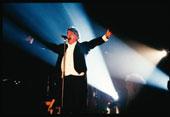"""Fabrizio De Andrè canta """"Ottocento"""" durante la tournée de """"Le nuvole"""", 1991 (foto Guido Harari)"""