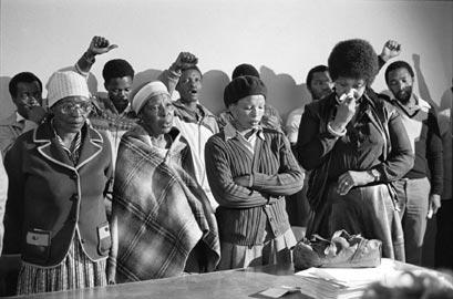 Gille de Vlieg, Pauline Moloise (madre di Ben), due donne e Winnie Madikizela Mandela piangono al servizio funebre per Benjamin Moloise, impiccato qualche ora prima di quella stessa mattina. Khotso House, Johannesburg, 18 ottobre  1985. © Gille de Vlieg.