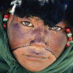 Tibet, Una ragazza nomade con il volto cosparso di una sostanza protettiva durante un pellegrinaggio, Tibet, Cina 1990 © Kazuyoshi Nomachi