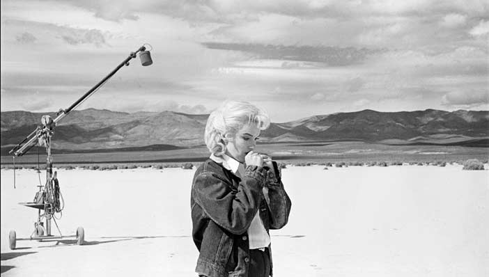 """© Eve Arnold / Magnum Photos USA. Nevada. US actress Marilyn MONROE on the Nevada desert going over her lines for a difficult scene she is about to play with Clarke GABLE in the film """"The Misfits"""" by John HUSTON. 1960 - Mostra Life – Magnum"""