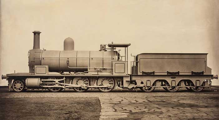 James Mudd, (Halifax, United Kingdom, 1821 / Bowdon, United Kingdom, 1906), Locomotiva a vapore, 1880 c., Steam Locomotive, c. 1880, Stampa al carbone, Mammoth Carbon Print, 83,8 × 121,3 cm (33 × 47 3/4 in.), © Courtesy Roland Belgrave Vintage Photography Ltd - In mostra alla Fondazione MAST di Bologna