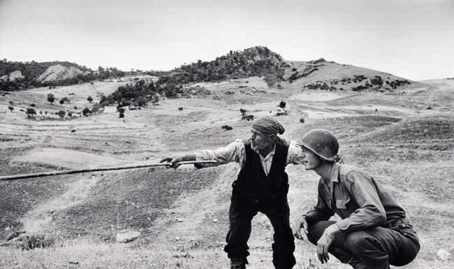 Contadino siciliano indica a un ufficiale americano la direzione presa dai tedeschi, nei pressi di Troina, Sicilia, 4-5 agosto 1943, © Robert Capa © International Center of Photography / Magnum Photos