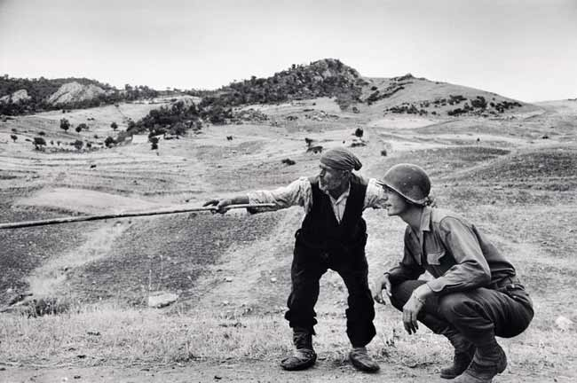 Contadino siciliano indica a un ufficiale americano la direzione presa dai tedeschi, nei pressi di Troina, Sicilia, 4-5 agosto 1943, © Robert Capa © International Center of Photography / Magnum Photos