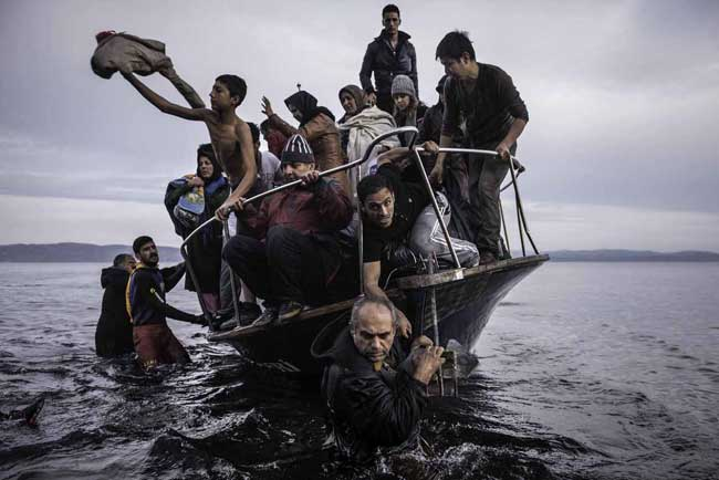 Sergey Ponomarev: Migrants arrive by a Turkish boat near the village of Skala, on the Greek island of Lesbos. Monday 16 November 2015. Series: Europe Migration Crisis, 2015 © Sergey Ponomarev, Prix Pictet 2017
